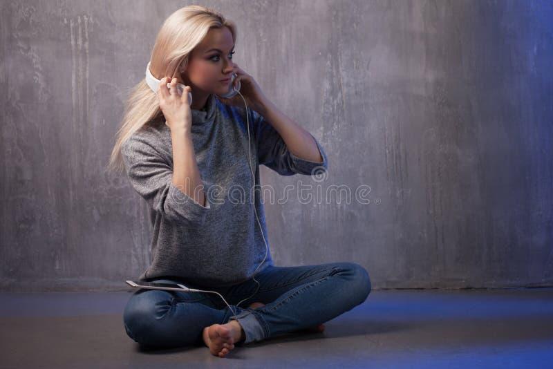 Menina com fones de ouvido, sentando-se no assoalho, escutando a música ou o rádio fotografia de stock royalty free