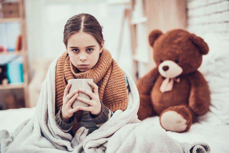 Menina com frio no lenço e na cobertura com a bebida quente nas mãos em casa imagens de stock royalty free