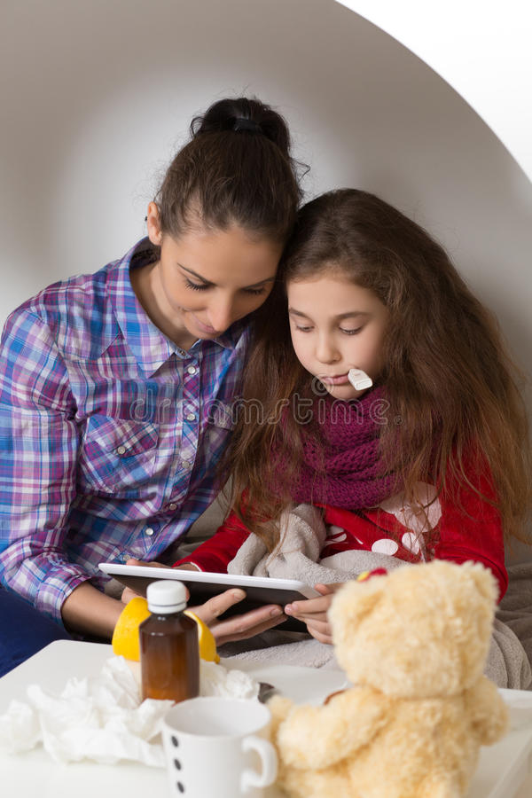 Menina com gripe, frio ou febre em casa imagens de stock