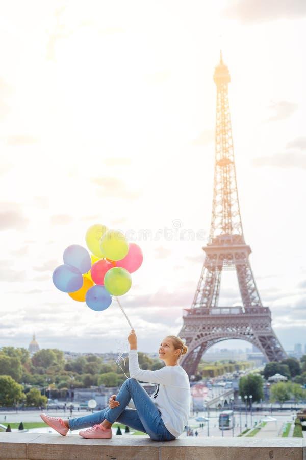 Menina com grupo de balões coloridos em Paris perto da torre Eiffel fotos de stock royalty free