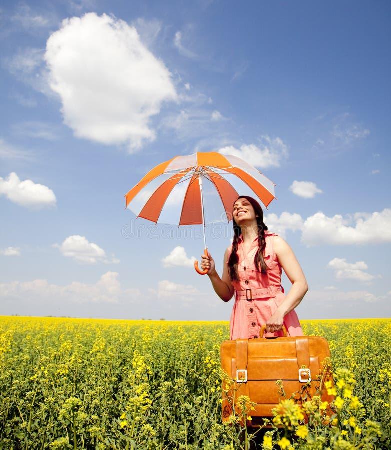 A menina com guarda-chuva e a mala de viagem na mola colocam. foto de stock royalty free