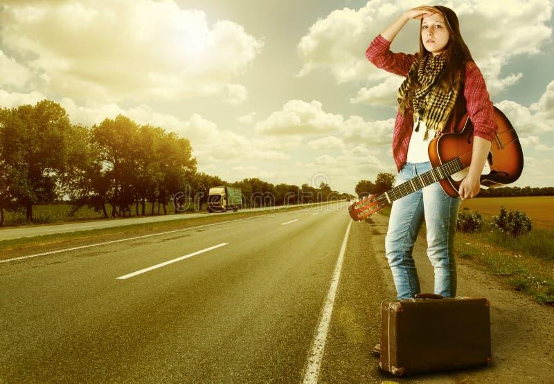Menina com guitare e mala de viagem na estrada fotos de stock royalty free