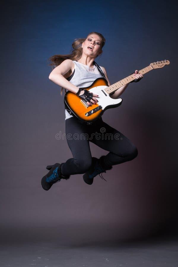 Menina com a guitarra no ensaio antes do desempenho foto de stock royalty free