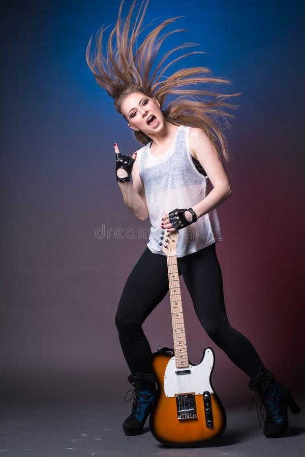 Menina com a guitarra no ensaio antes do desempenho fotografia de stock