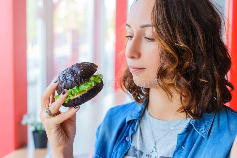 Menina com hamburguer preto fotos de stock royalty free