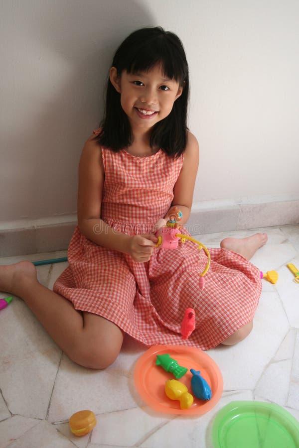 Menina com a haste de pesca do brinquedo fotografia de stock royalty free