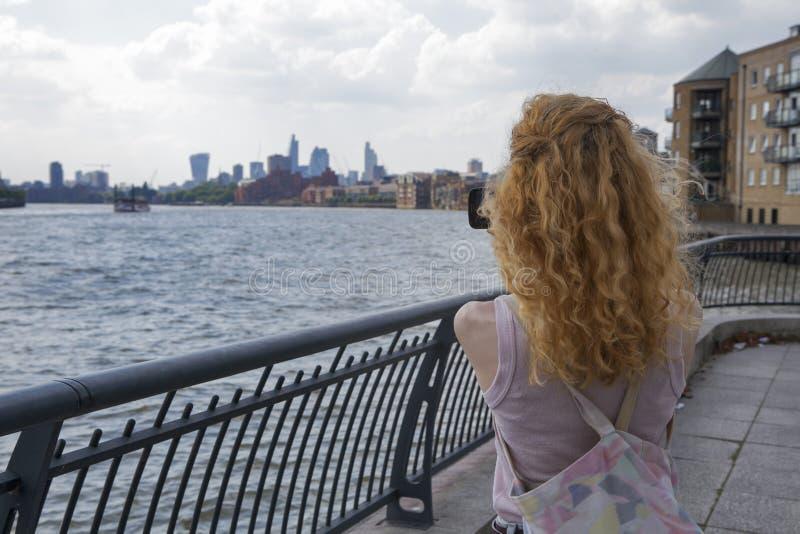 A menina com imagens vermelhas do cabelo da Tamisa e Londres telefonam fotografia de stock