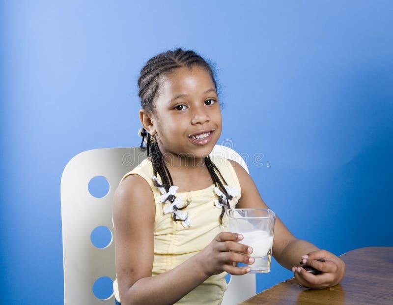 Menina com leite e bolinhos imagens de stock