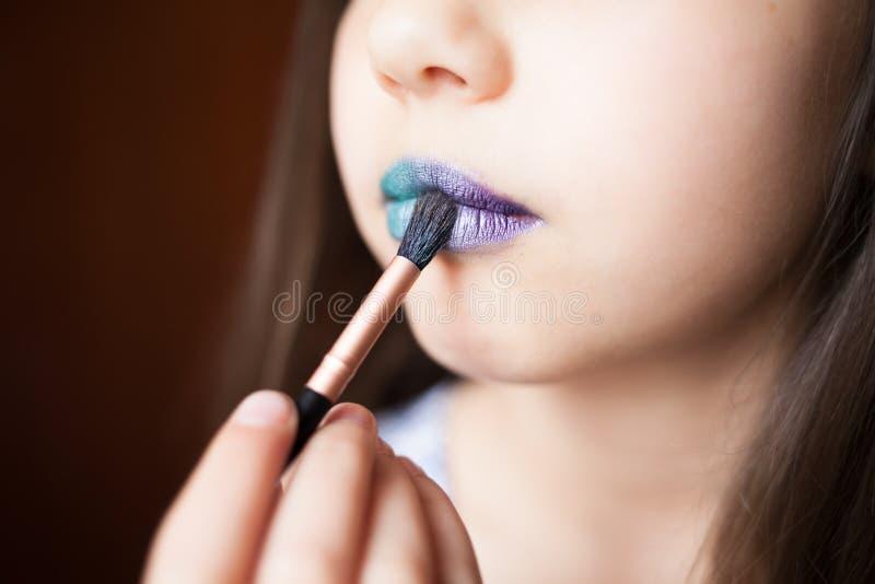 Menina com lipsteak azul em seus bordos imagens de stock royalty free