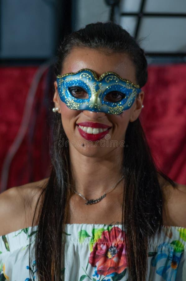 Menina com máscara do carnaval e vestido curto com teste padrão viscoso floral Modelo com roupa elegante Moça com muito particul imagem de stock royalty free