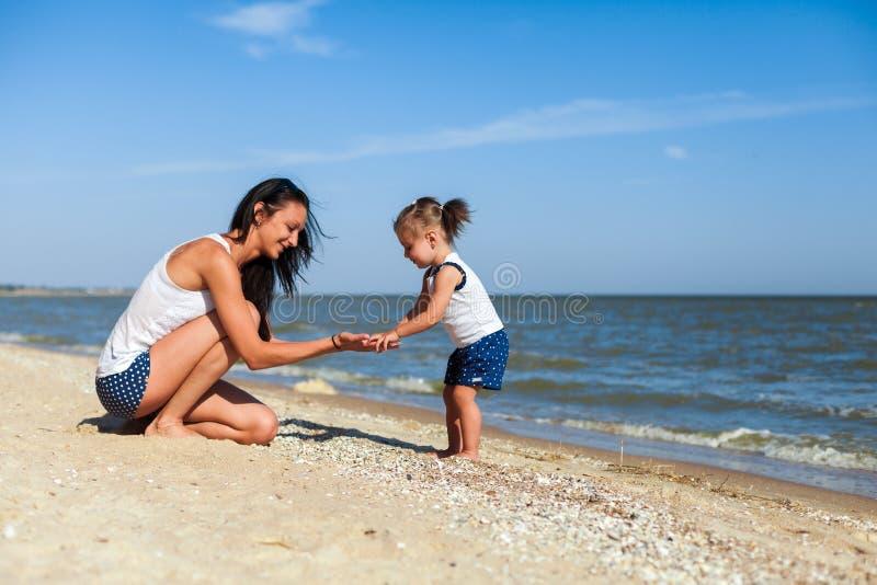 Menina com a mãe na praia pelo mar fotos de stock