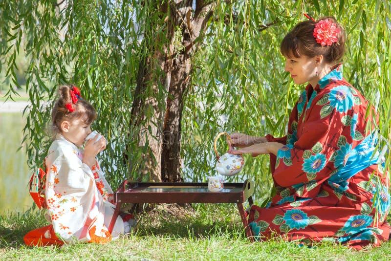 Menina com a mãe no quimono que senta-se ao lado da tabela de chá fotos de stock
