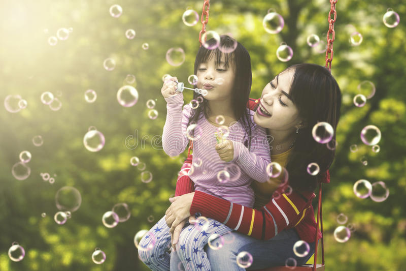 Menina com a mãe que joga bolhas de sabão imagens de stock royalty free