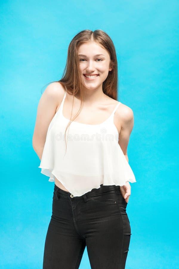 A menina com mãos em uns bolsos sorri amplamente fotos de stock