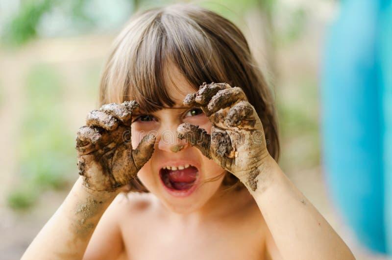 Menina com mãos enlameadas fotografia de stock