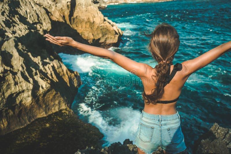 A menina com mãos levantadas aprecia a vista para o mar imagens de stock