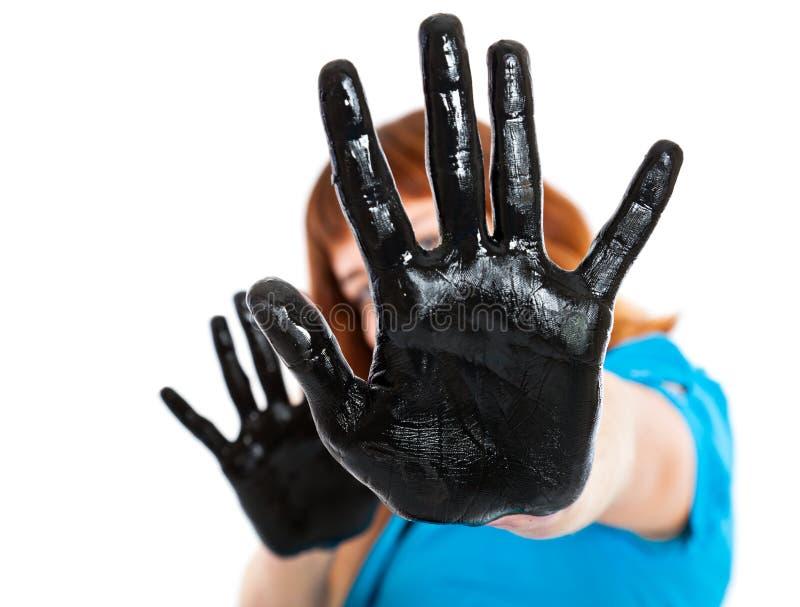 Menina com mãos na pintura preta fotos de stock