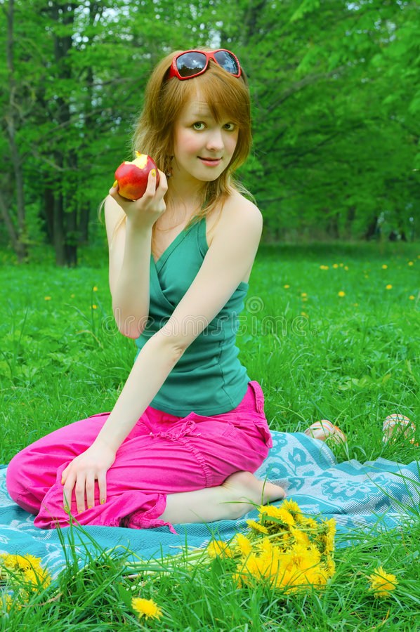 Menina com a maçã no coverlet foto de stock royalty free