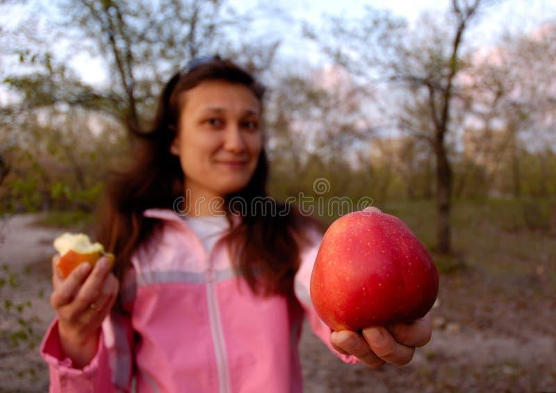 Menina com a maçã vermelha grande em sua mão imagem de stock