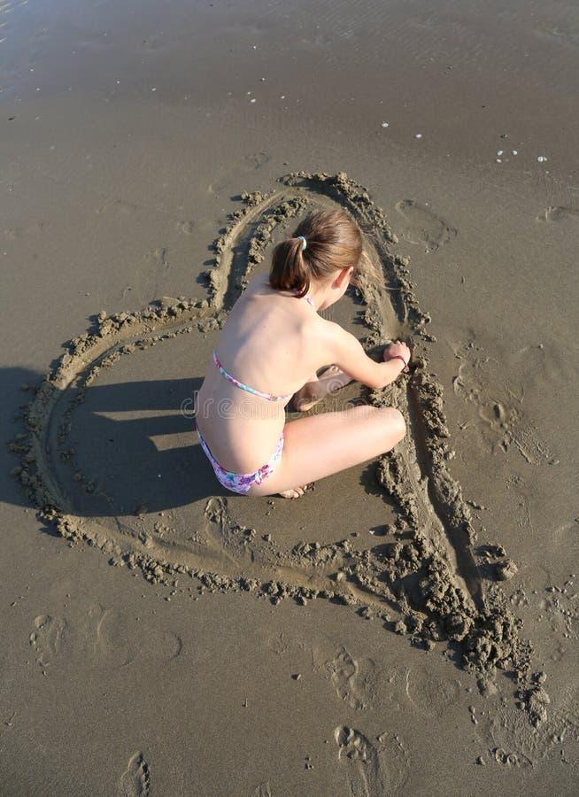 A menina com maiô tira um coração na areia molhada de t imagens de stock