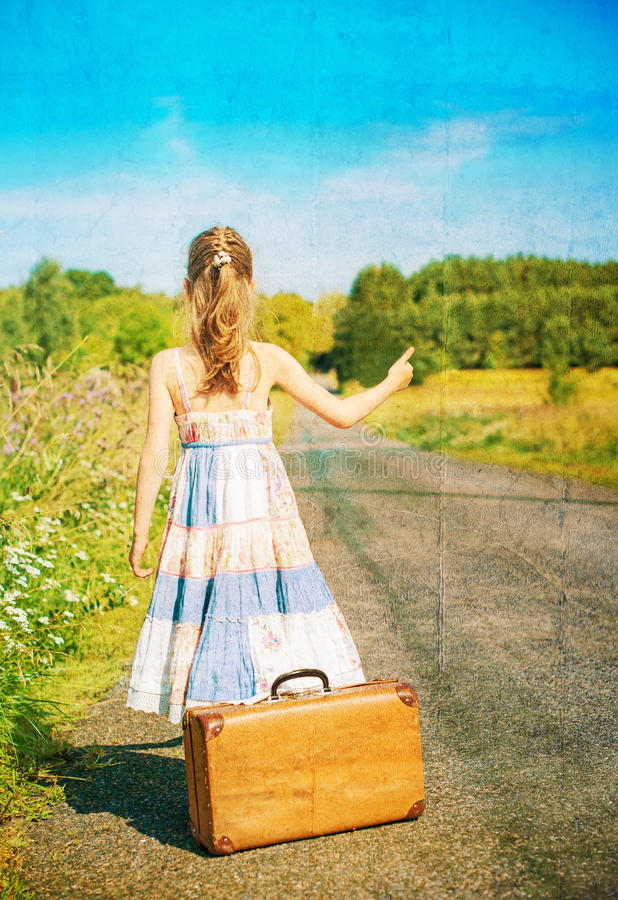 Menina com a mala de viagem na estrada rural imagens de stock