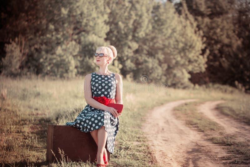 menina com a mala de viagem no campo imagem de stock