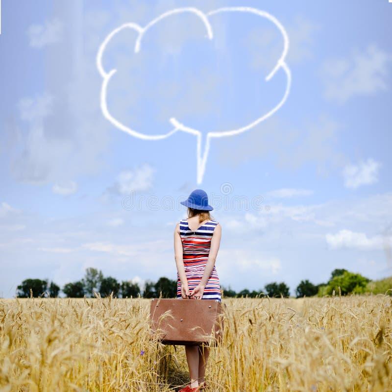 Menina com a mala de viagem que está no campo de trigo com foto de stock