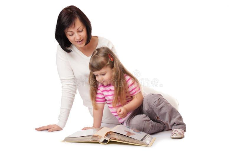 A menina com matriz olha o álbum da família imagens de stock