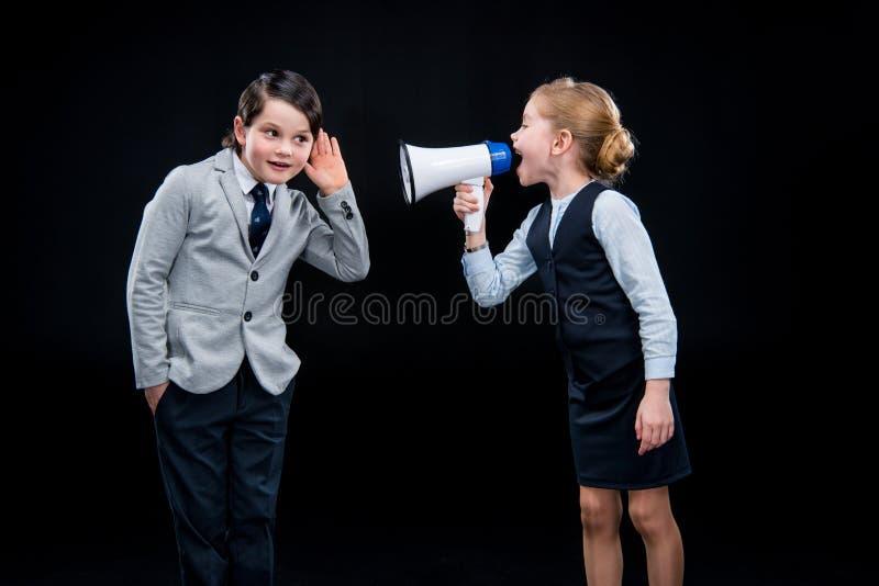 Menina com megafone que grita no menino imagem de stock