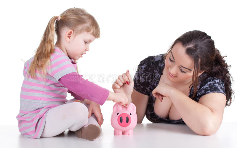 Menina com mulher nova e o banco piggy imagem de stock