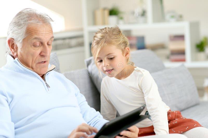Menina com o avô que senta-se no sofá usando a tabuleta foto de stock royalty free
