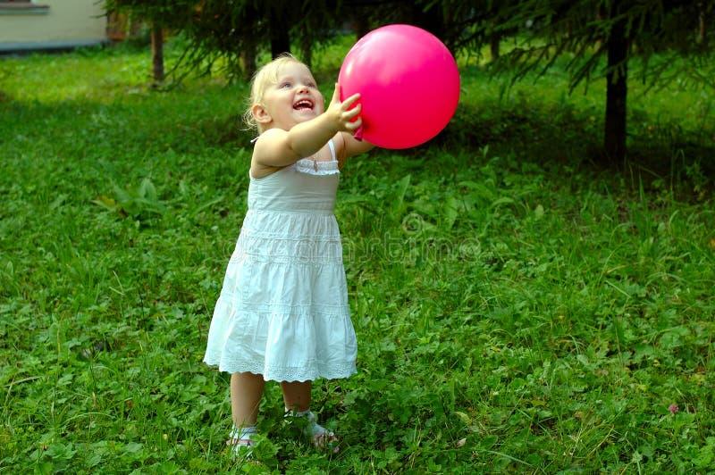 Menina com o balão vermelho na floresta. imagens de stock royalty free