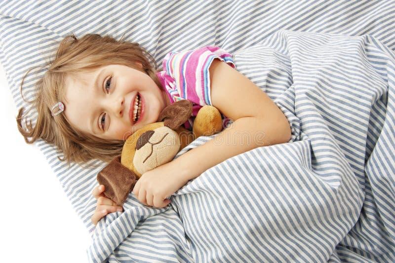 Menina com o brinquedo na cama foto de stock