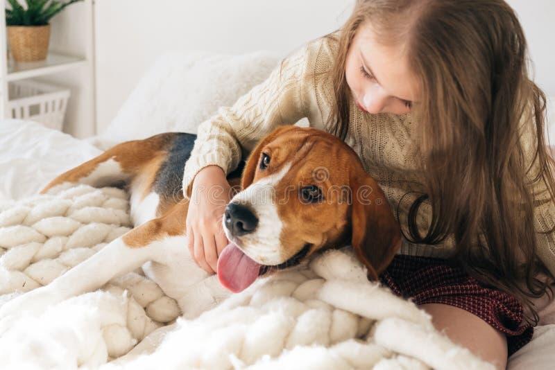 Menina com o cão que encontra-se na cama e no riso foto de stock royalty free