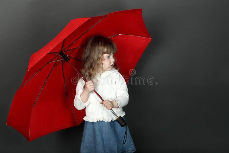 Menina com o cabelo de fluxo que está sob o guarda-chuva imagens de stock