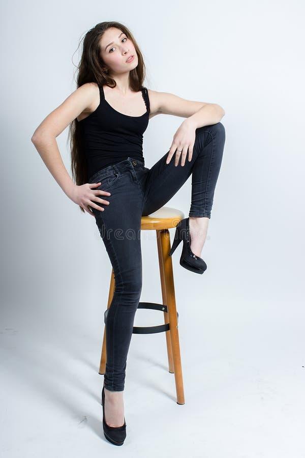 Menina com o cabelo escuro longo que levanta na cadeira, calças de brim pretas da camiseta de alças imagens de stock royalty free