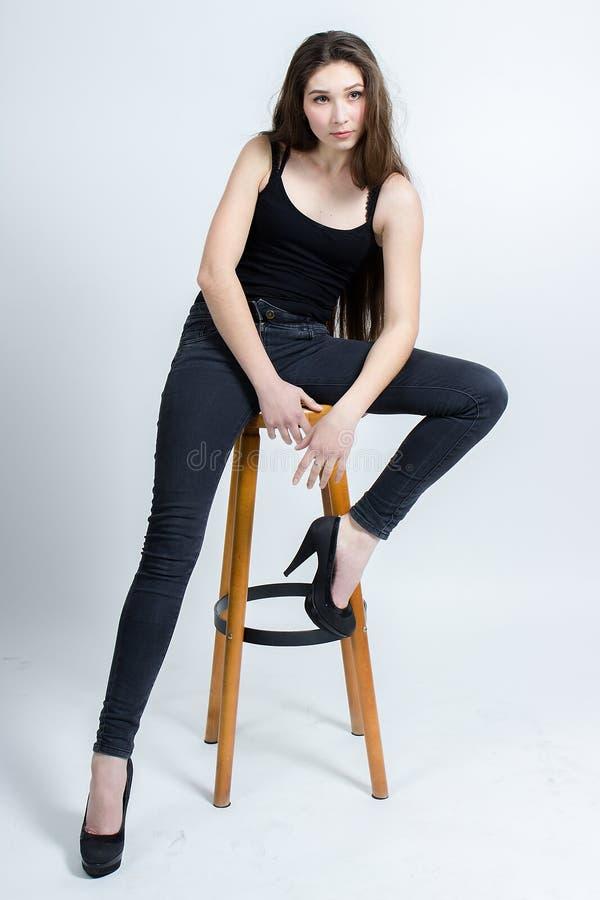 Menina com o cabelo escuro longo que levanta na cadeira, calças de brim pretas da camiseta de alças fotografia de stock royalty free