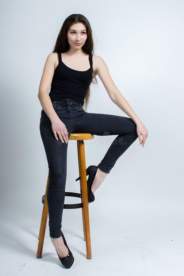 Menina com o cabelo escuro longo que levanta na cadeira, calças de brim pretas da camiseta de alças fotografia de stock