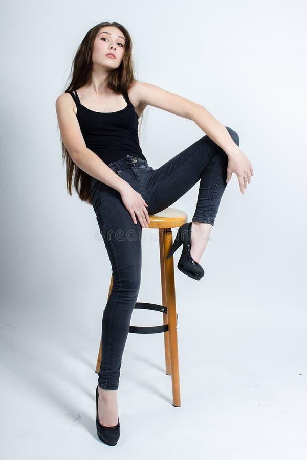 Menina com o cabelo escuro longo que levanta na cadeira, calças de brim pretas da camiseta de alças fotos de stock royalty free