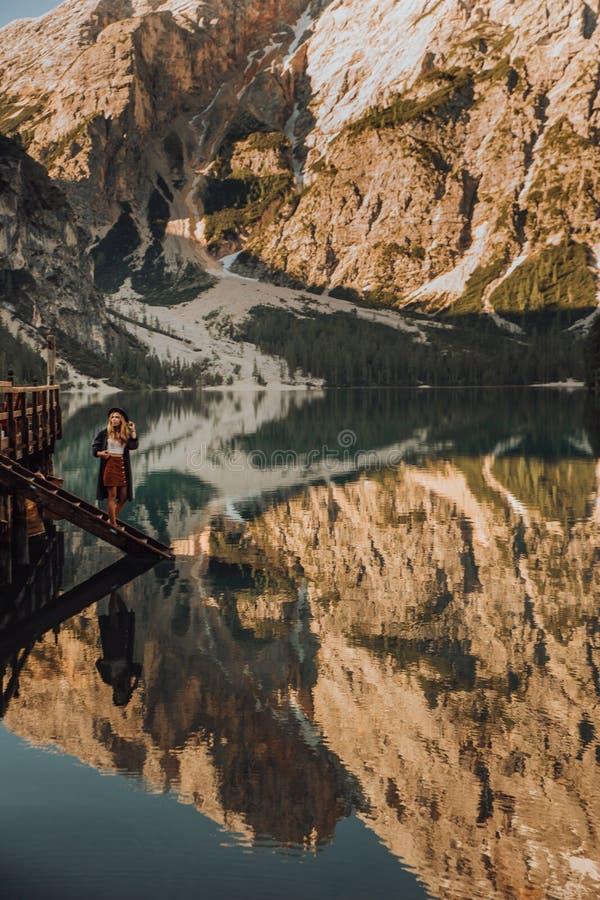 A menina com o cabelo longo que veste um chapéu largo-brimmed e uma camisa listrados em um fundo de Lago Lago di Braies no imagens de stock royalty free