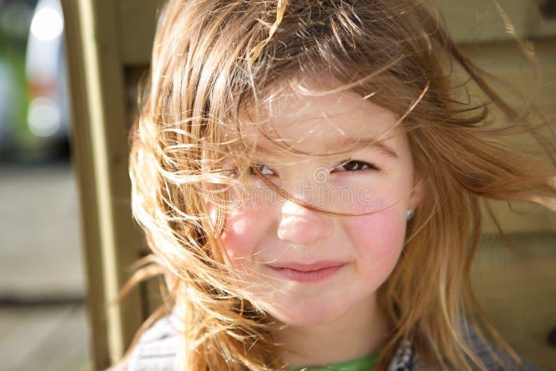 Menina com o cabelo que funde na cara imagens de stock royalty free