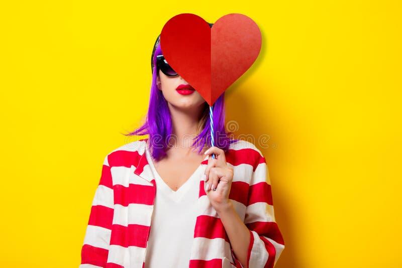 Menina com o cabelo roxo que guarda a forma do coração fotos de stock royalty free