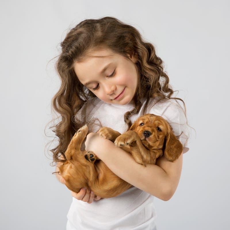 Menina com o cachorrinho isolado no fundo branco Amizade do animal de estimação da criança imagem de stock