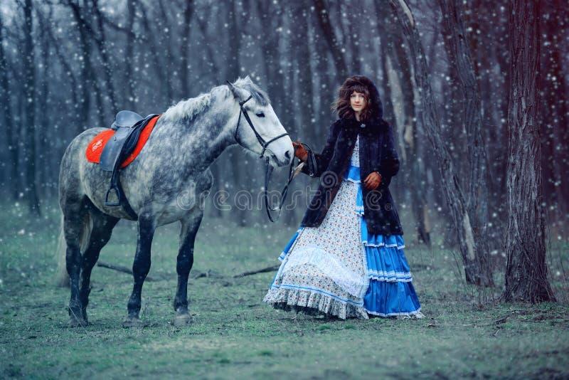 Menina com o cavalo no inverno imagens de stock