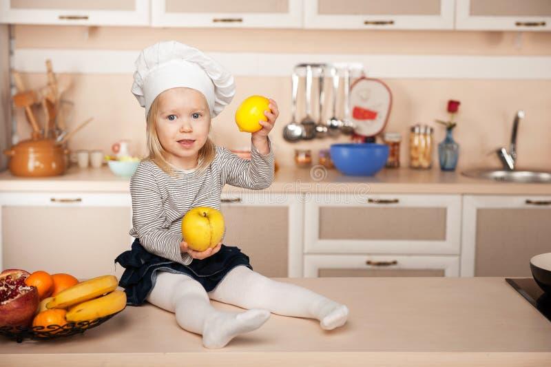 Menina com o chapéu do cozinheiro chefe que guarda frutos quando fotografia de stock