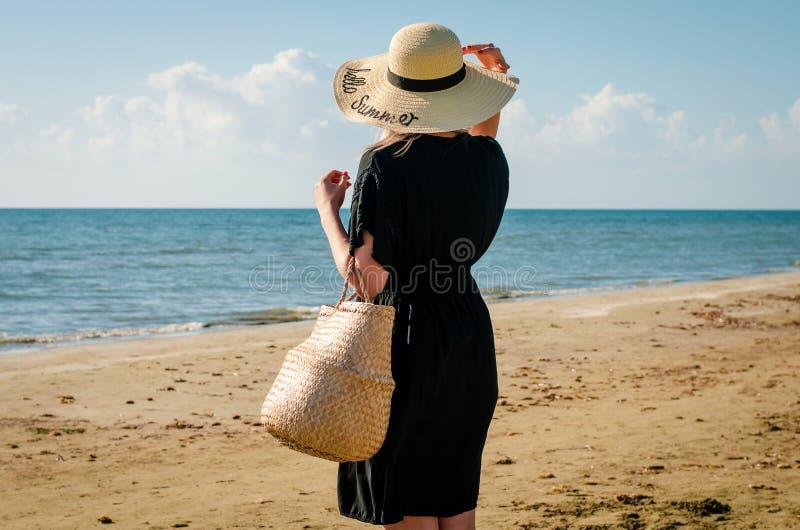 Menina com o chapéu preto do vestido e de palha que relaxa na praia de Corfu no por do sol fotos de stock royalty free