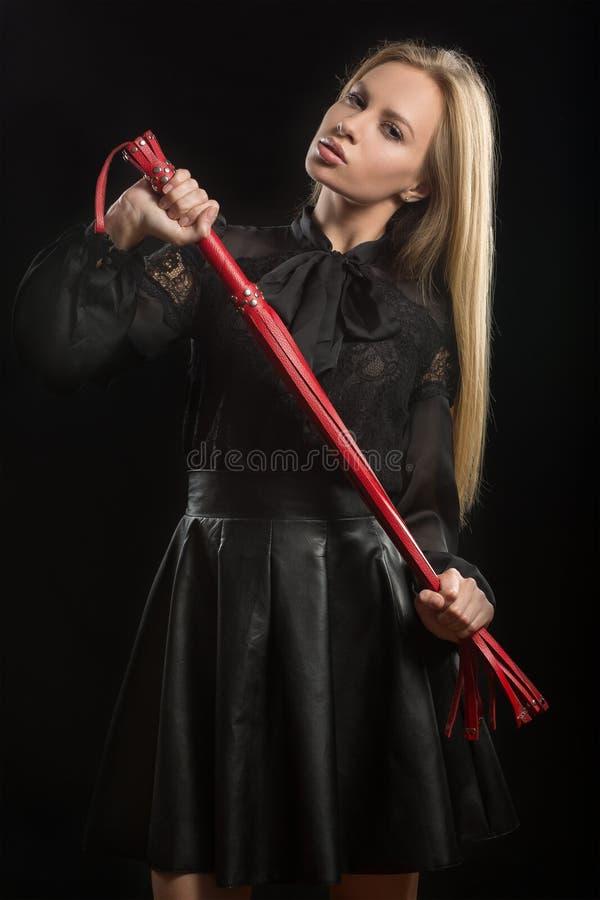 Menina com o chicote de couro vermelho fotografia de stock royalty free