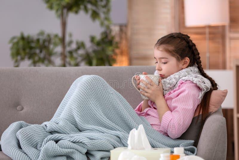 Menina com o copo da bebida quente que sofre do frio no sofá imagem de stock