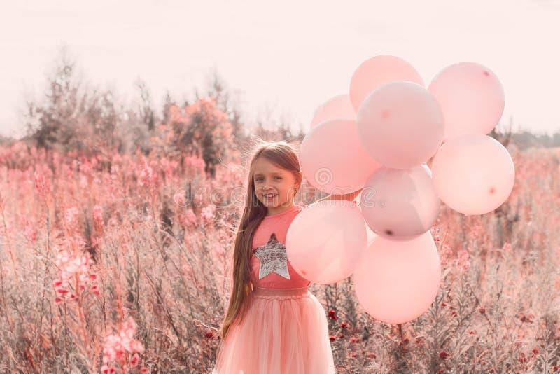Menina com o coral na moda dos balões tonificado imagens de stock royalty free