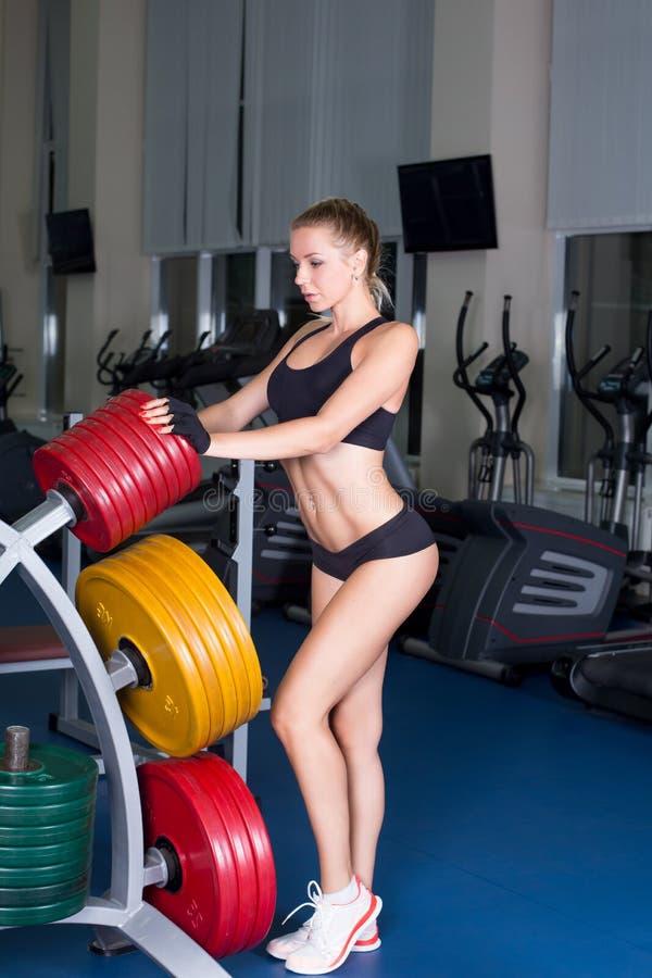 Menina com o corpo perfeito que executa o exercício do barbell foto de stock royalty free